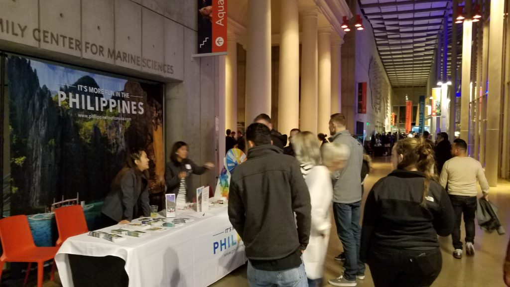 <photo> PDOT-San Francisco team Alessa Lopez and Nadine Tanjuakio engaging event goers to spin the wheel for promotional giveaways and answering inquiries about Philippine destinations.